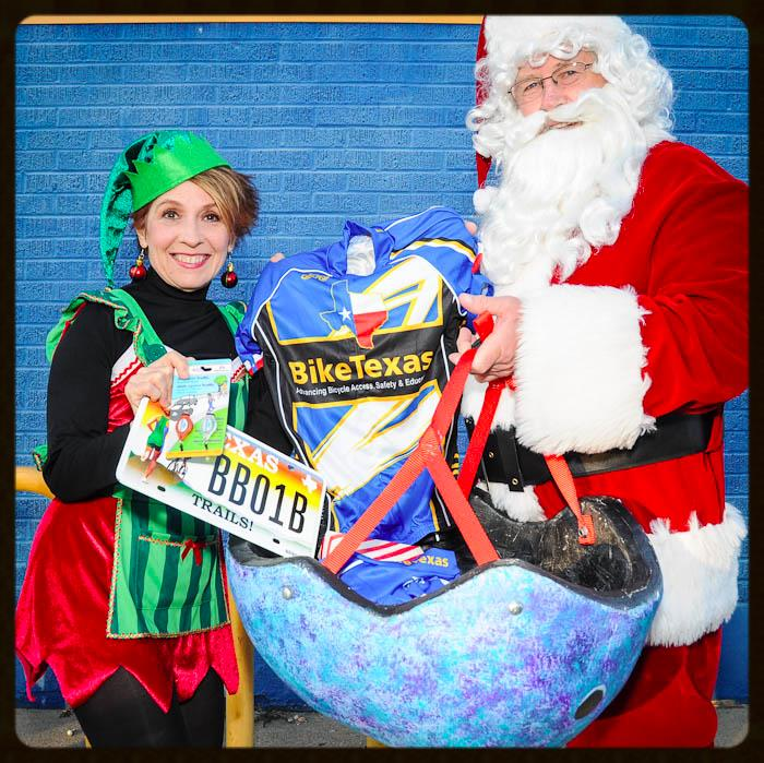 Santa and an elf with BikeTexas merchandise
