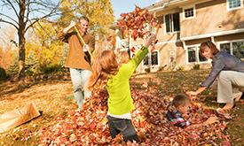 Family Raking And Playing In Leaves