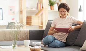 Woman On Tablet On Couch
