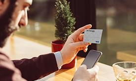 Businessman holding Debit Card while on phone
