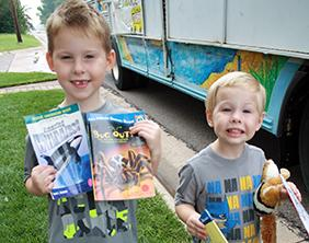 Two boys smile with their books from the Summer Bookmobile.
