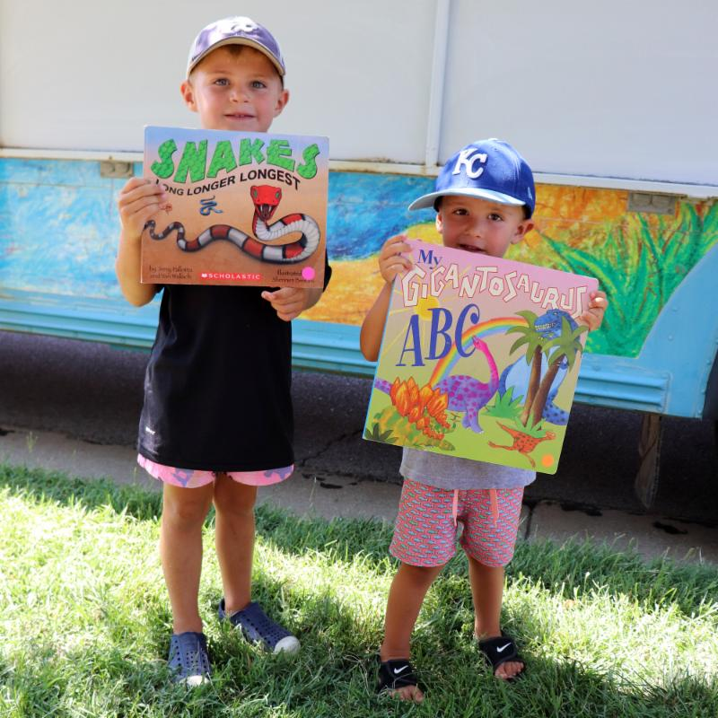 Two boys pose with their books from the Summer Bookmobile.