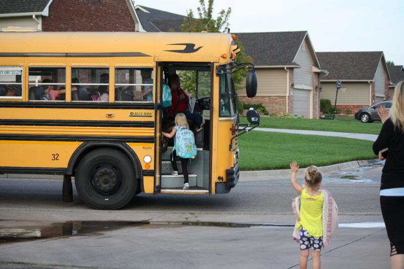 A student boards a Maize USD 266 school bus on the first day of school in August 2017.