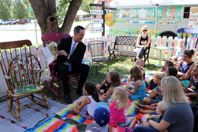 Dr. Chad Higgins, Superintendent of Maize Schools, reads to a crowd of children and community members during the annual Super Story Time event at MOXI Junction.