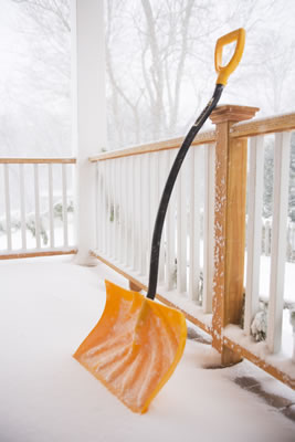 A shovel is propped up on a snowy porch.