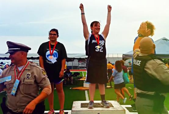 A Special Olympics Kansas athlete celebrates her first-place finish.