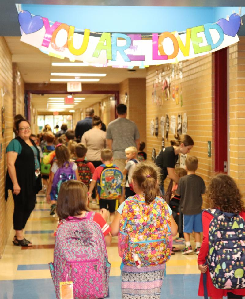 Students walk down the hallways together at school.