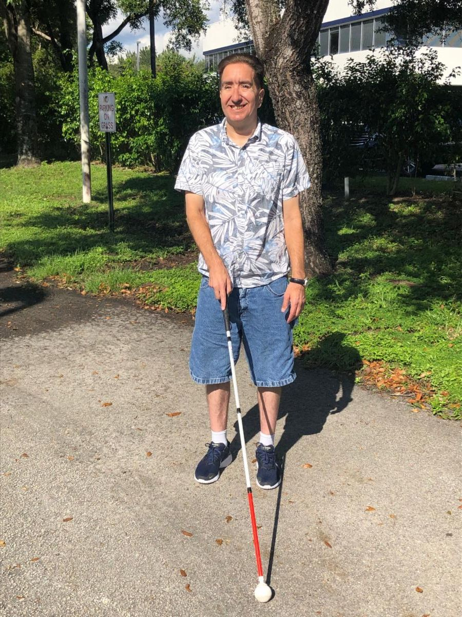man in a light blue shirt and denim shorts walking with a white cane