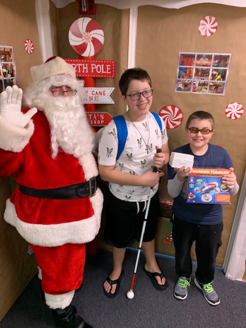 Santa standing with two young blind boys holding a white cane and presents