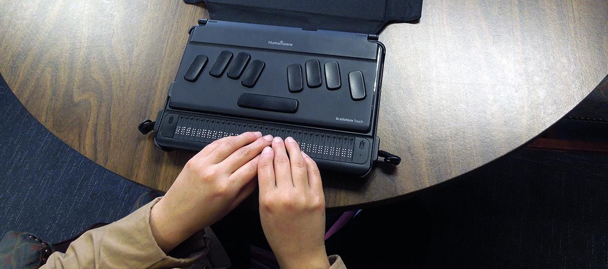 2 hands on a braille notetaker