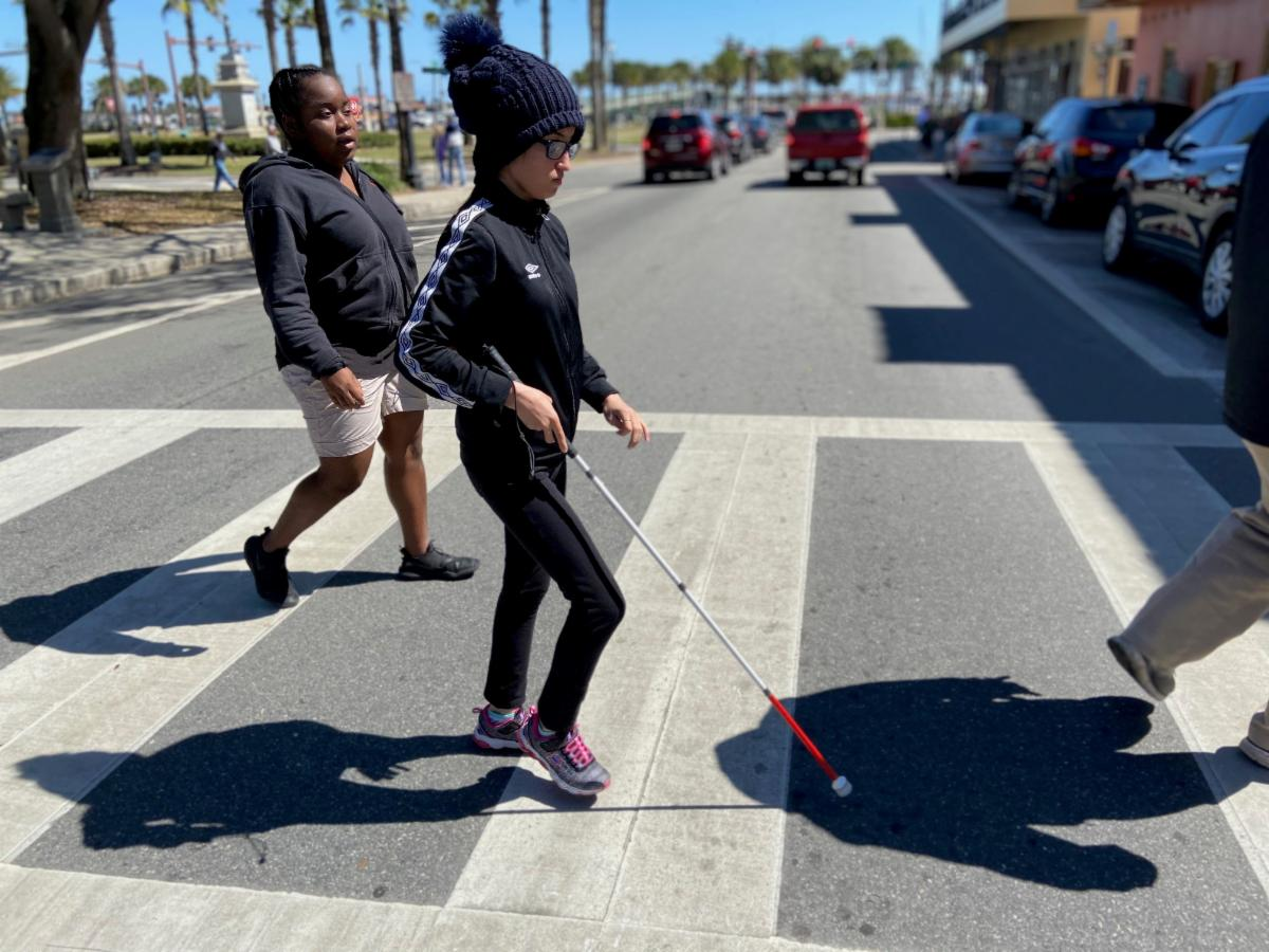 Two students walking across a busy street at a crosswalk with a white cane