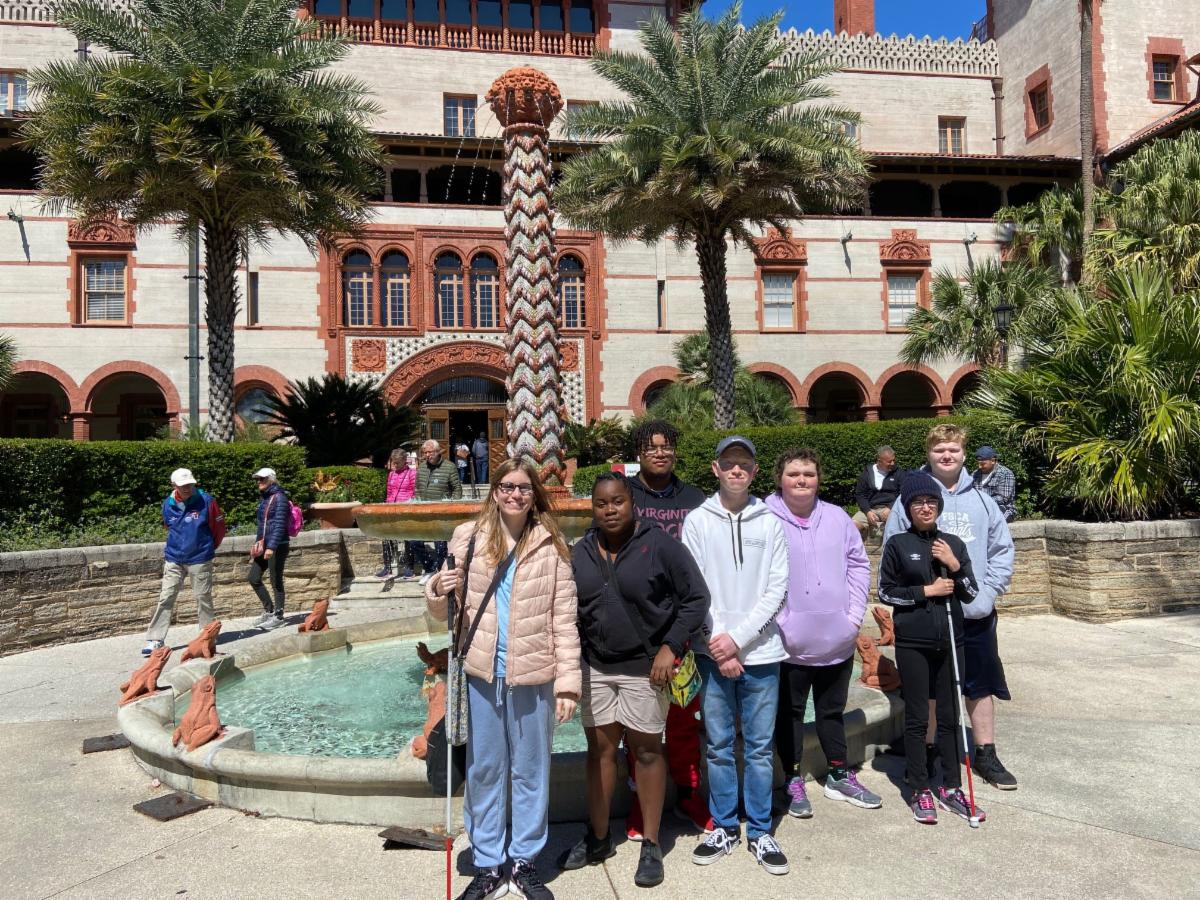 Seven students pose in front of a fountain