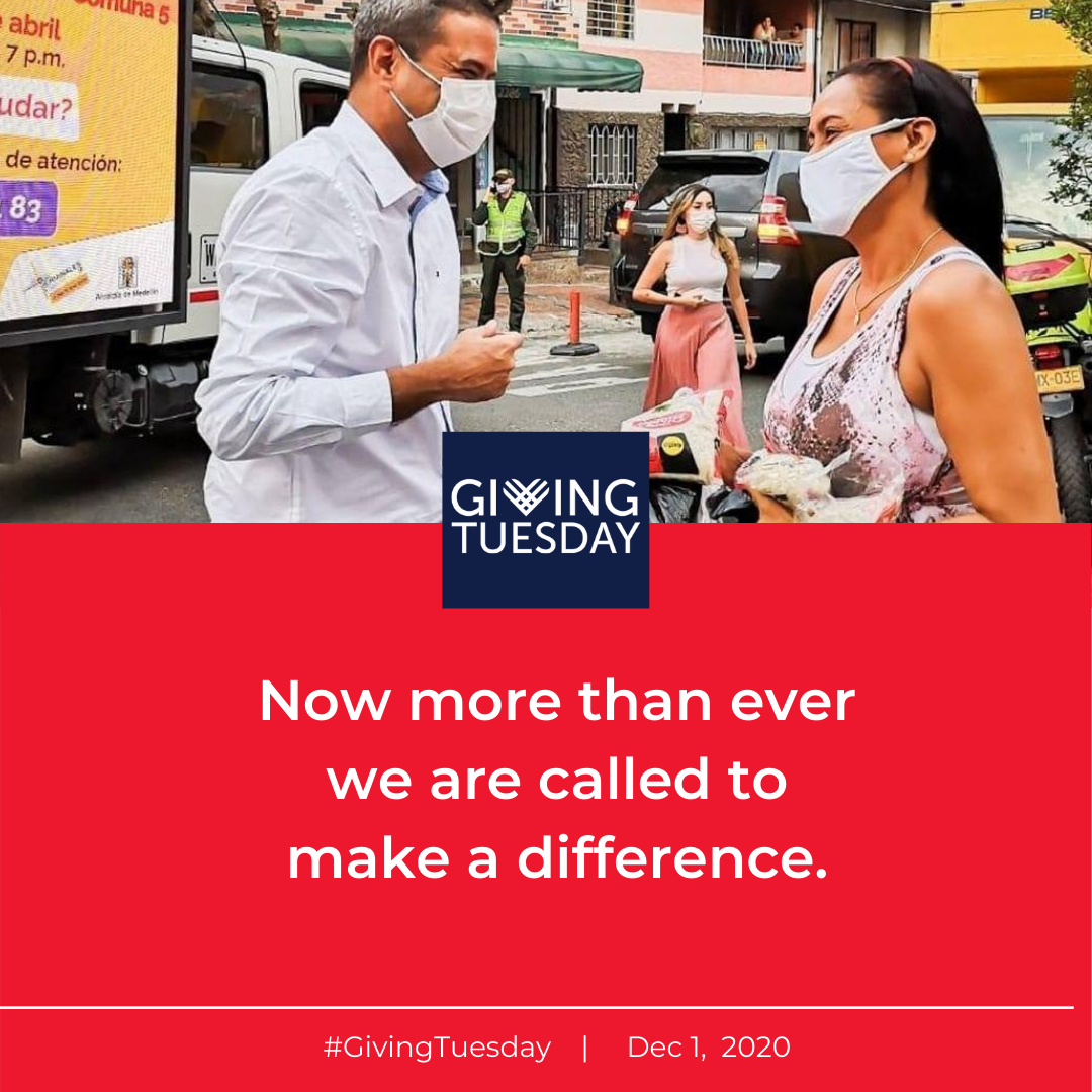 man with a mask talking to a woman in a mask with the words Giving Tuesday in a blue box.