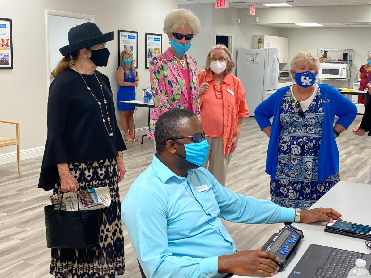 Winston Callum demonstrates assistive technology devices to several masked women