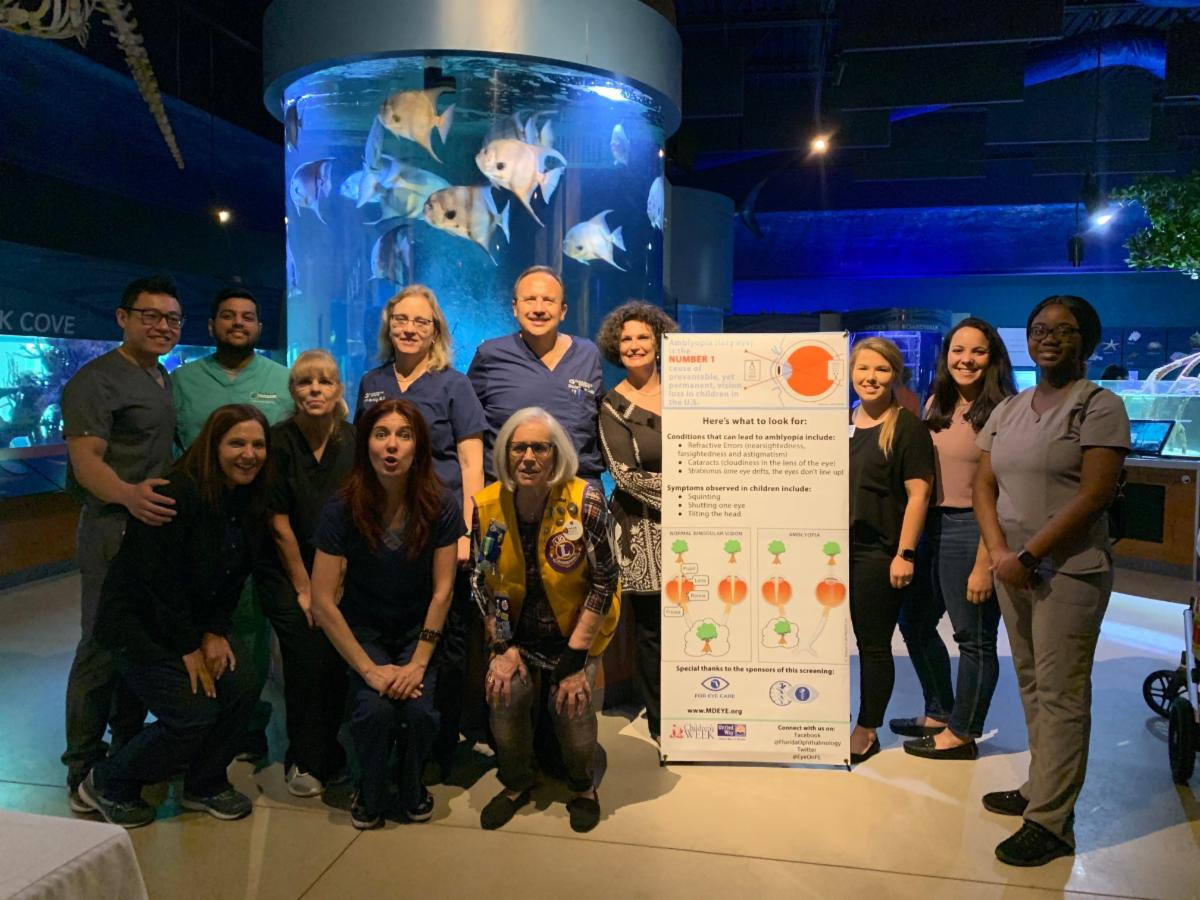 Lighthouse staff and volunteers from Lions Club and Florida Ophthalmologist Association pose in front of an aquarium