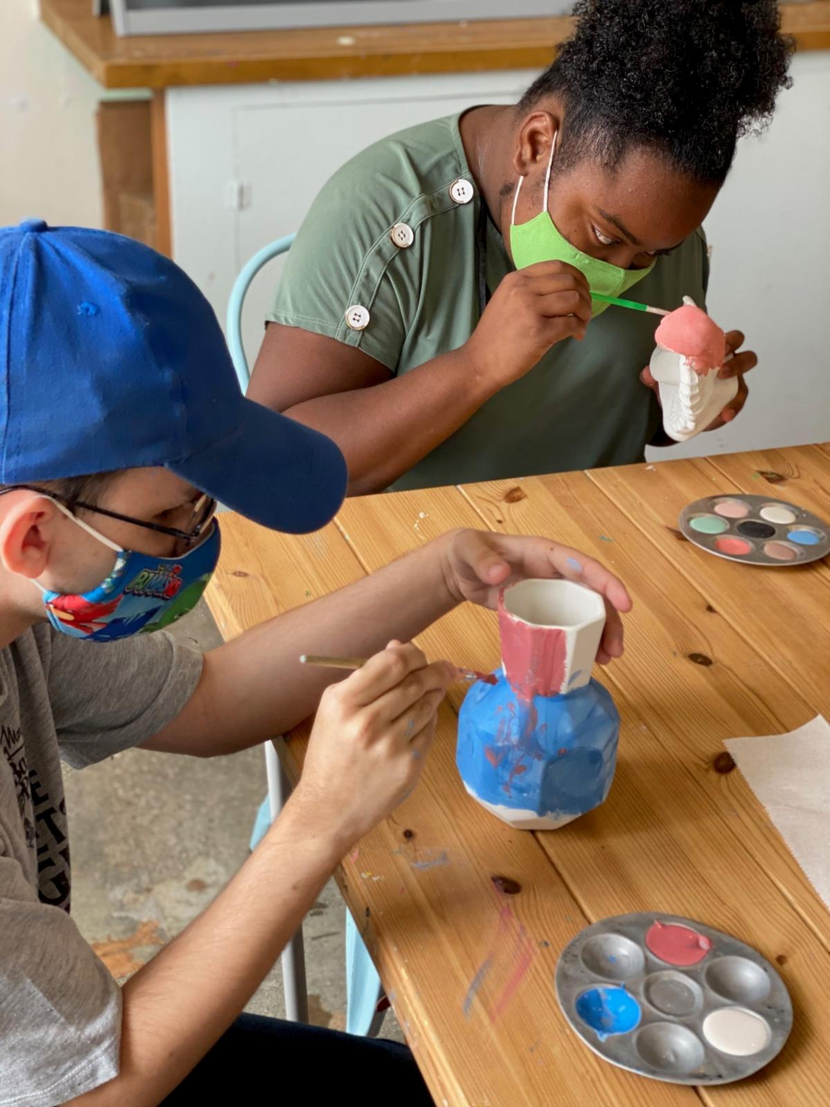 A boy and a girl painting pottery at a table