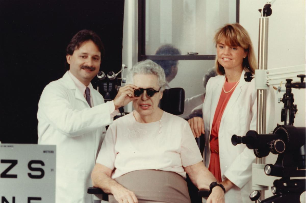 Dr Gartner with a female patient sitting in a chair with an assistant watching