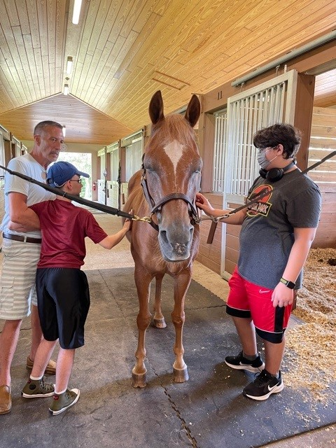 Instructor Curt helps two teens groom a brown horse in a stable