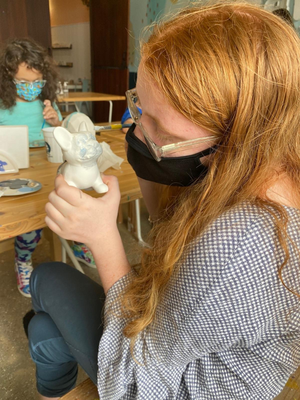 Young red head girl painting a pottery dog