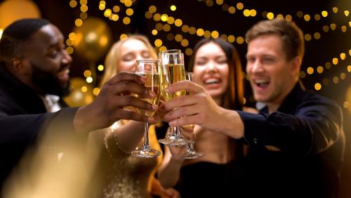 Happy multi-ethnic company clinking beverage glasses_ celebrating New Year