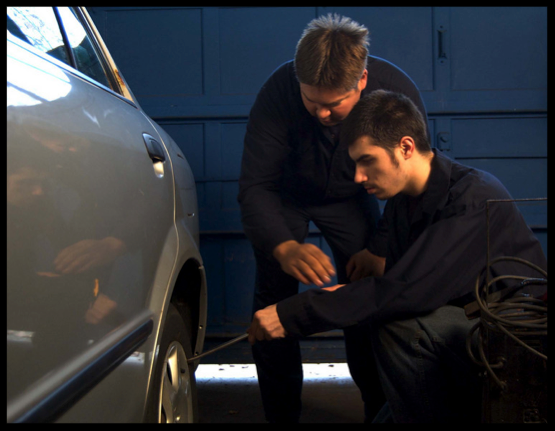 Two white males work on a car tire