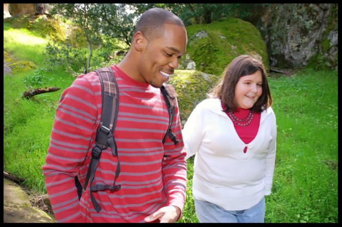 Black man and white woman walking outside.