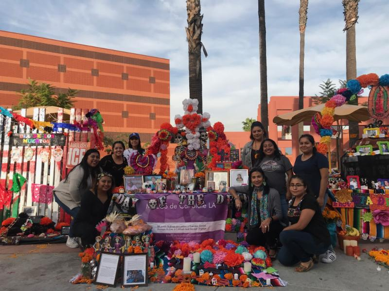Students and faculty gathered around a Dia De Los Muerto alter. They are smiling at the camera.