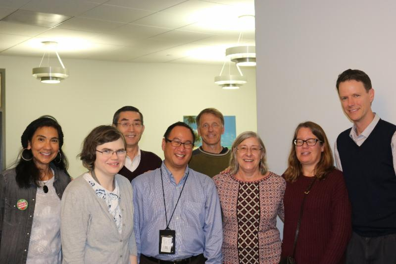 Gene Sandan (center) surrounded by NSS faculty and staff. All standing in a hallway and smiling for the camera.