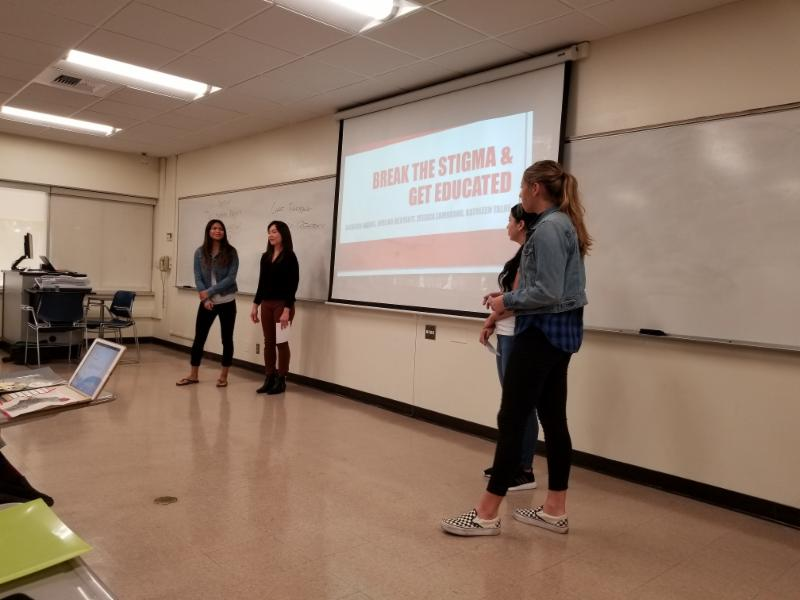 Four students giving presentation in a classroom. Students refer to powerpoint during presentation