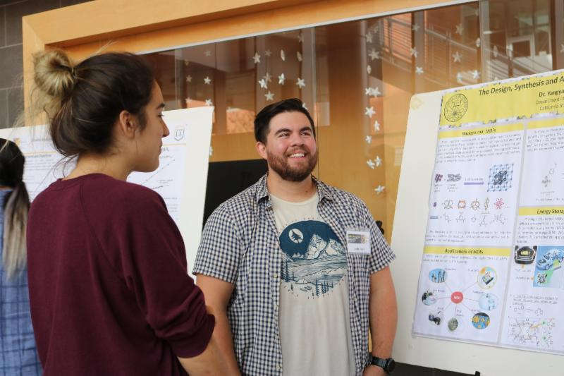 Male student in front of a presentation poster board smiling. Female student looking at the poster board.