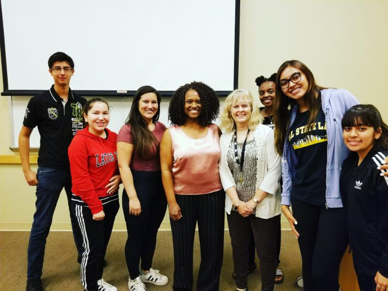 Six students from the pre-med club posing with Dr. McQueen and a female guest speaker