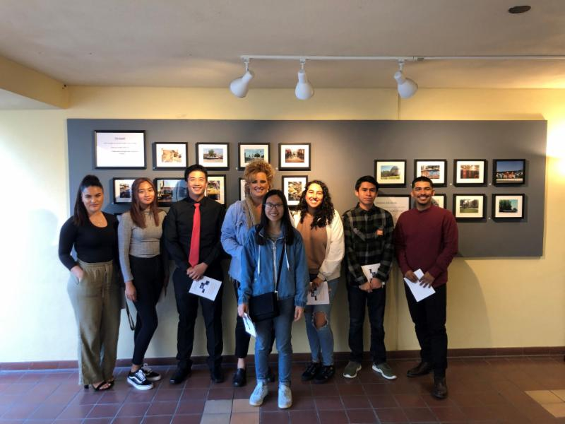 Seven students and Dr. Dawn Dennis stand in front of their exhibition and smile for the camera.