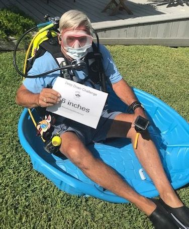 Ed sitting in baby swimming pool  with scuba gear on