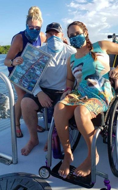 Allison in her wheelchair with a shark print tank dress with Hellen and captain John