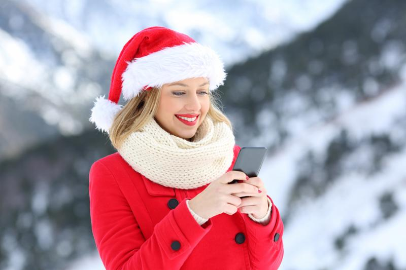 Portrait of a happy girl sending christmas messages on a smart phone on holidays with a snowy mountain in the background