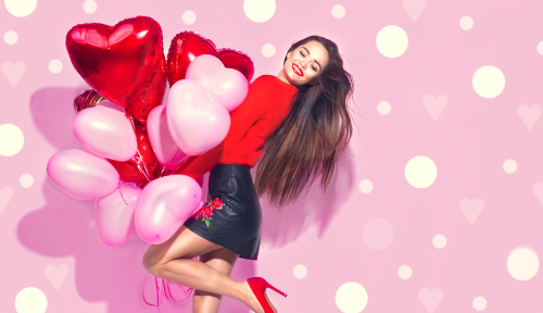 Valentine Beauty girl with red and pink air balloons laughing_ on pink polka dots background. Beautiful Happy Young woman. holiday party. Joyful model posing_ having fun_ celebrating  Valentine s Day