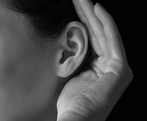 Unrecognizable woman holds her hand near ear and listens_ close-up