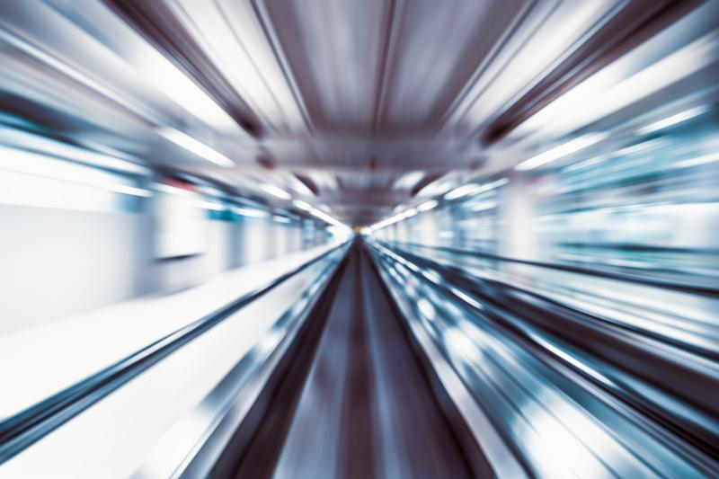 Motion blur abstract background_ fast moving walkway or travelator in airport terminal transit_ zoom effect_ center diminishing perspective. Transportation_ warp speed_ or business technology concept