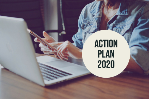 Action plan 2020 with young freelance woman using smartphone and laptop in modern workspace_ new year resolution concept