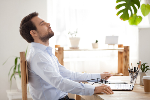 Satisfied calm businessman taking break to relax finished work sitting at desk enjoying stress free job breathing fresh air_ happy executive manager resting at workplace dreaming in quiet office