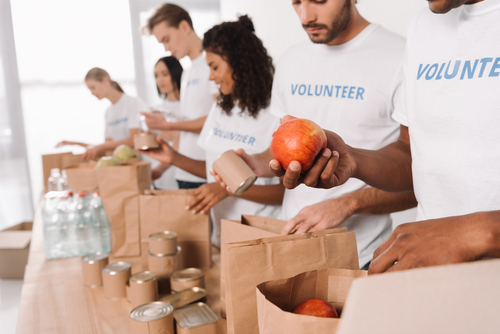 group of multiethnic volunteers putting food and drinks into paper bags for charity