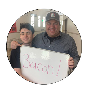 Jim Angelus and student hold up sign that says_ Bacon_