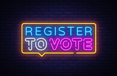 register to vote in neon lights against a brick wall