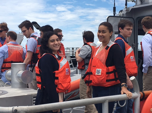 Smiling students in life vests stand on the deck of a boat.