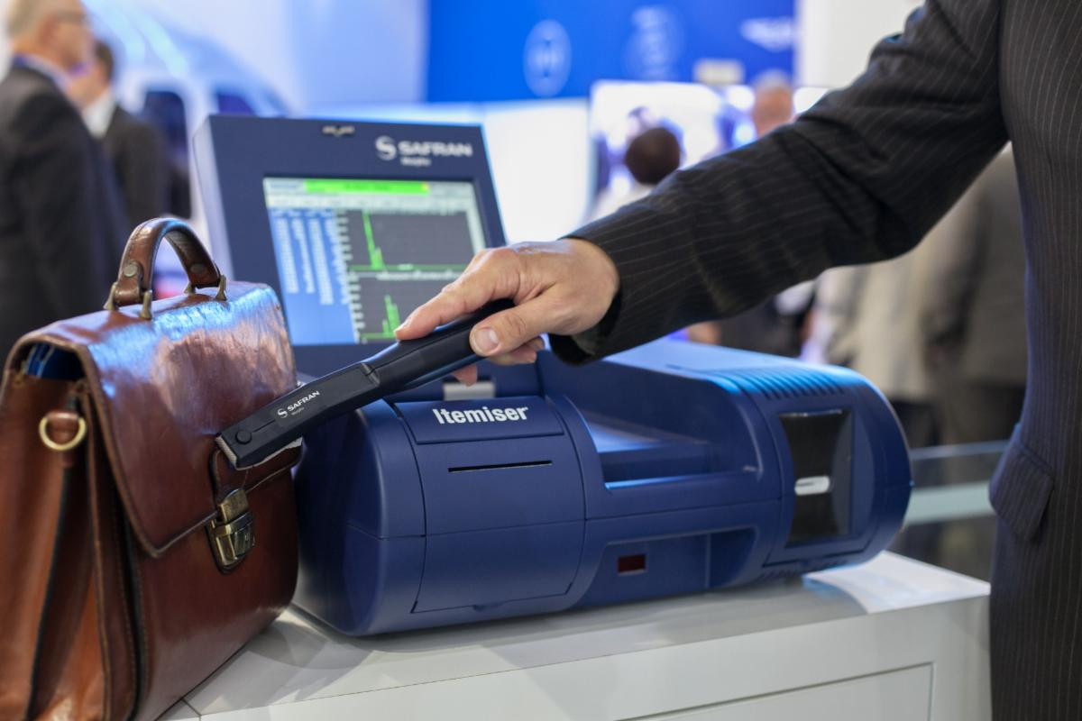 """An example of an explosives trace detection scanner used in airports from Morpho Detection. A hand holds a scanning wand over a piece of baggage next to a machine with the word """"Itemiser"""" on it."""