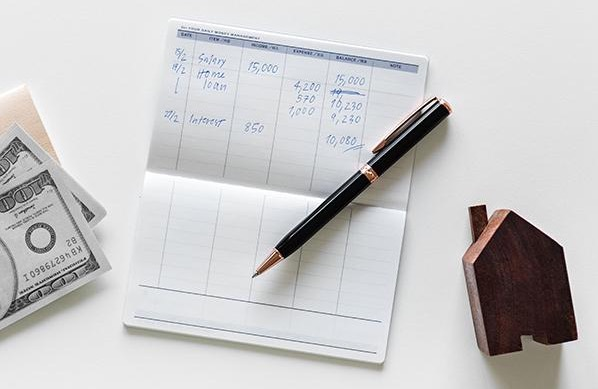 checkbook house pen and cash on a white surface