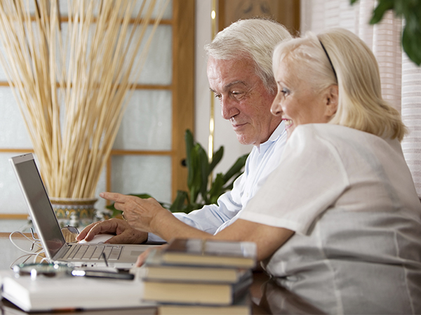 Senior man and woman sitting together in front of a laptop