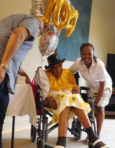 Woman in wheelchair with 2 people and balloon