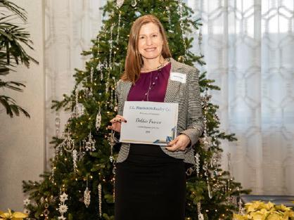 woman with award in front of Christmas tree