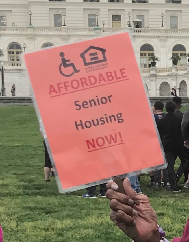 hand holding sign that says Affordable Senior Housing Now!
